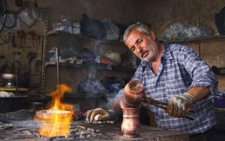 elderly man holding and working on copper items fire in front of him