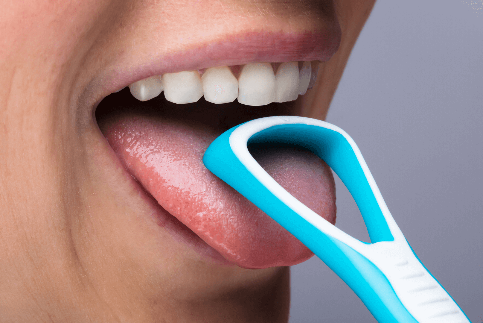 close up on person's mouth tongue out plastic tongue scraper