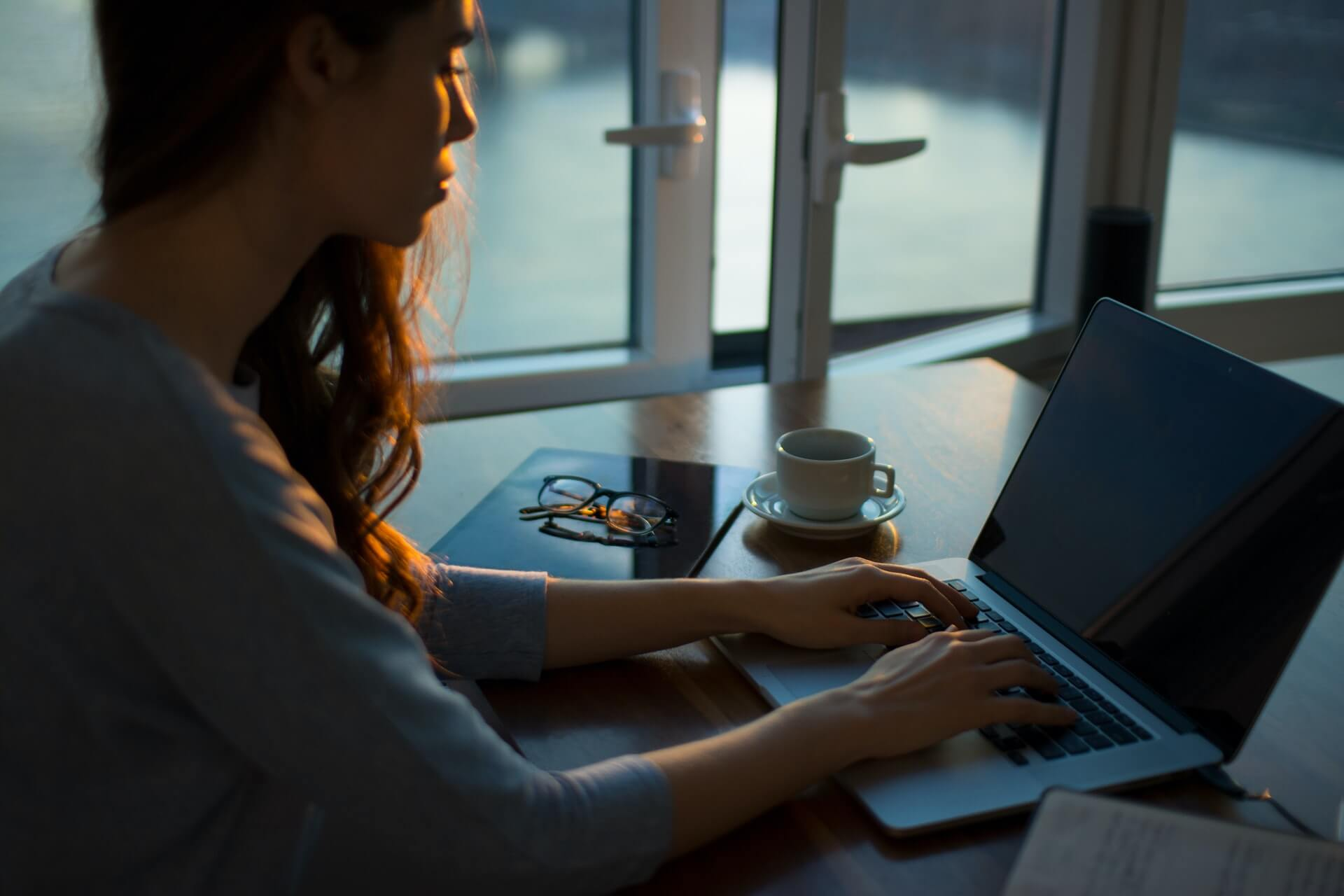 woman sitting beside table using laptop white mug and glasses on the surface