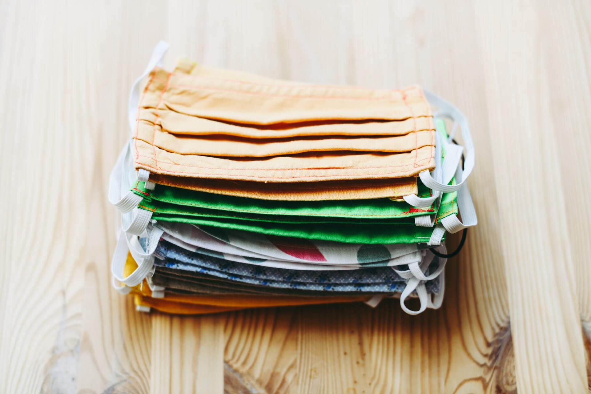 stack of many pieces fabric face masks assorted colors and design