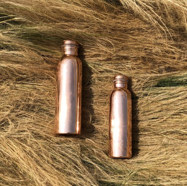 two Copper H2O smooth polished copper water bottles placed on hay