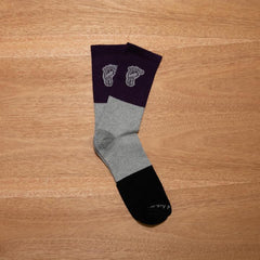 Pair of Purple, Grey, and Black socks on a wood background