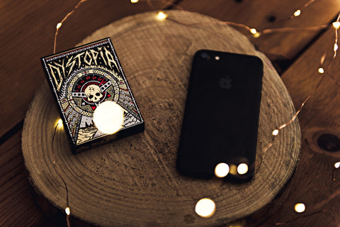 Apple iPhone and Dystopia Playing Cards resting on a wood platform