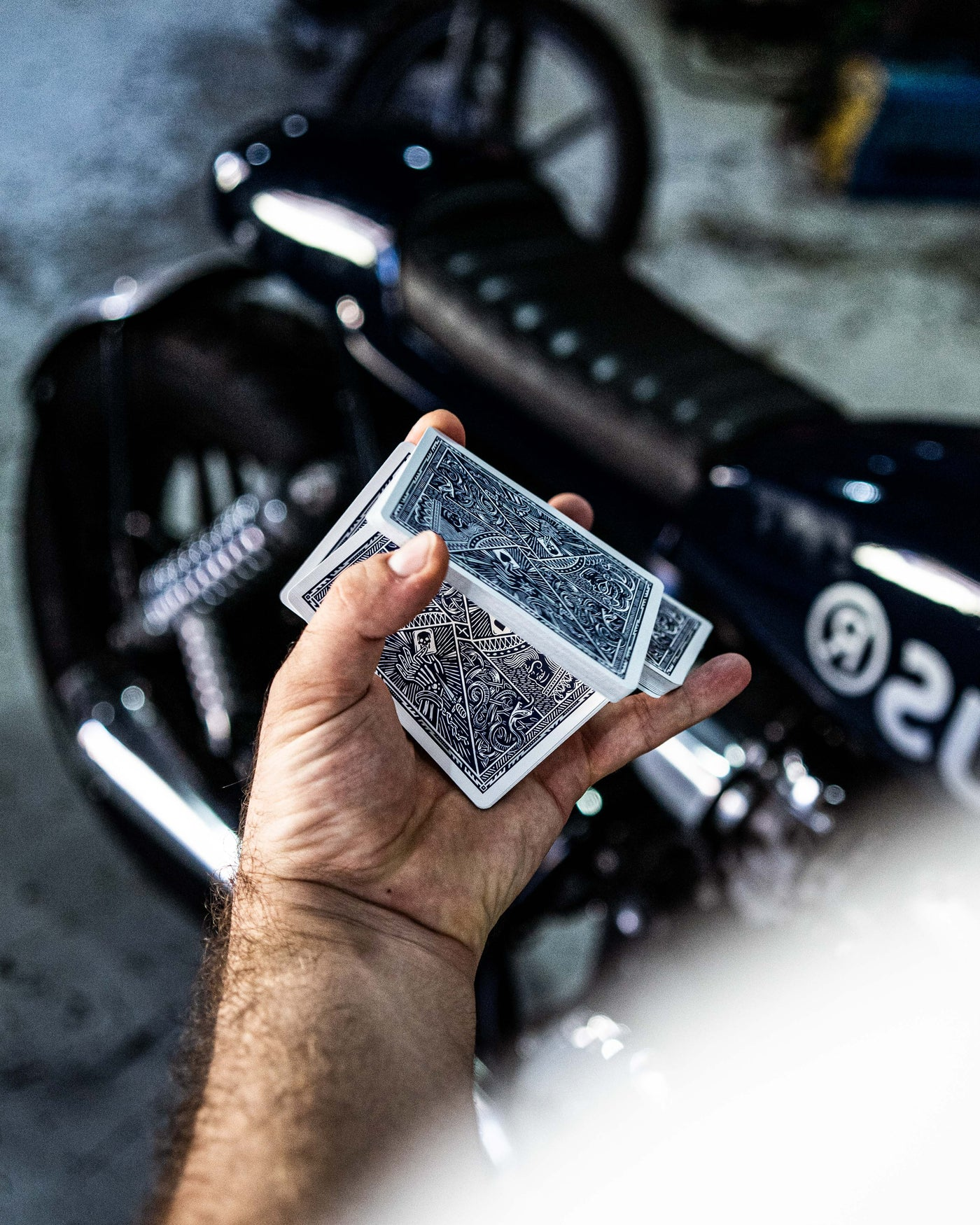 Playing cards held in a hand while performing one handed cut cardistry move in front of a custom motorcycle from Deus Ex Machina