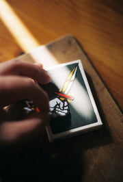 A left hand carefully applying the dagger sticker to the surface of a deck of playing cards