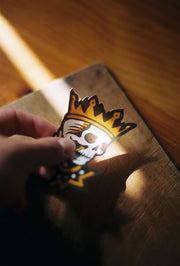 Holding the skull kings head sticker in the fingers of the left hadn't above a wooden surface with a light ray illuminating the subject of the image
