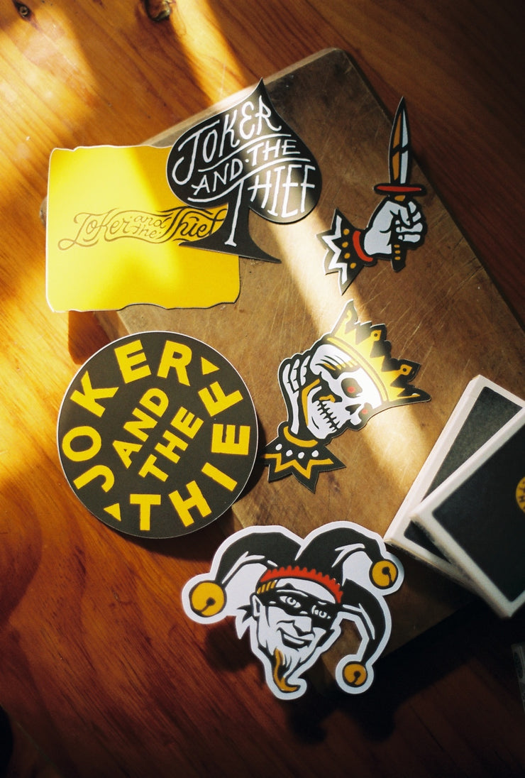 Six sticker laying on a wooden table with light rays casting light upon them. They sit next to two decks of 597 playing cards by Joker and the Thief. One sticker is a spade, the other a yellow distressed rectangle with the company logo, a round logo sticker, a kings head sticker, a jokers head sticker and a hand holding a knife