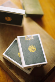 Three decks of Five Ninety-Seven playing cards displayed on a wooden surface. Clearly visible are the lettepressed embossing elements and the deck's custom perforated seal.