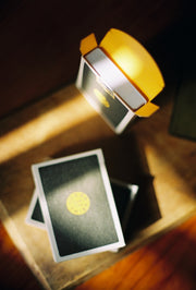 A top down view of the interior of the 597 playing cards, revealing a bright yellow letterpress box interior. Two decks sit on a wooden surface beside the upright deck of playing cards