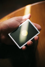 A light ray leaks over a green deck of Joker and the Thief playing card being held in the palm of a hand. The centre of the back design displays the company logo.