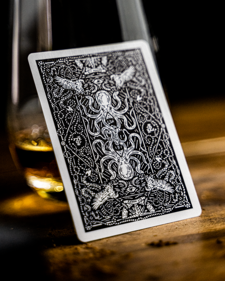 The Black Seafarers back design leaning upon a glass filled with whisky, on a textured wooden surface.