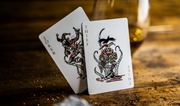 The custom motif jokers of the Joker and the Thief brand stand upright on a wooden surface with a glass of whiskey in the background. The lighting illuminated the card's metallic ink and vibrant red inks