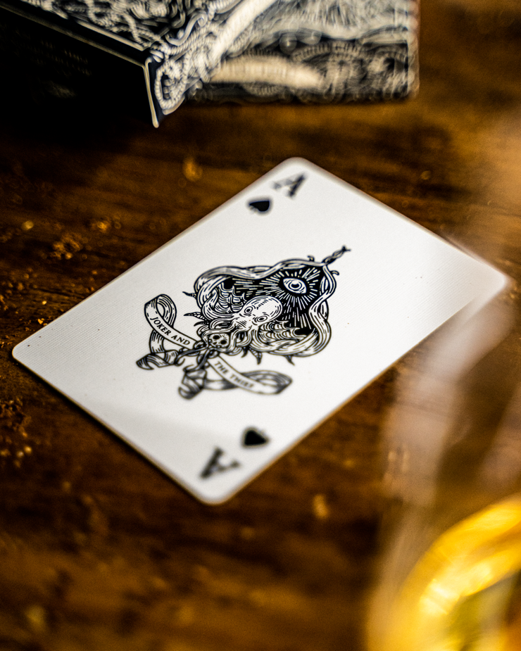 The nautical ace of spades from Joker and the Thief's seafarers playing cards lays diagonally on a wooden surface. In the foreground is blurred glass and in the background are two decks of playing cards stacked on top of one another.
