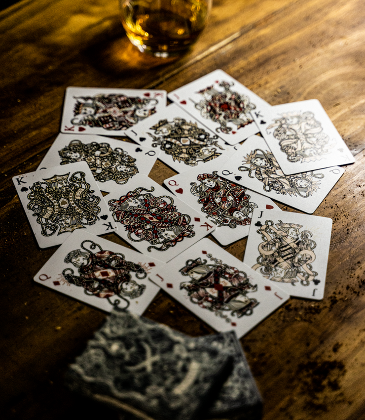 All twelve custom court cards of seafarers playing cards. Each card is displayed on a wooden table, with each royal sporting metallic ink.