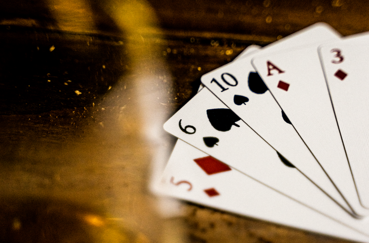 A close up shot of an example of the custom face cards of Seafarers Playing Cards. The image sees the five of diamonds, six of spades, ten of spades, ace of diamonds, and three of diamonds, fanned out on top of a wooden surface.