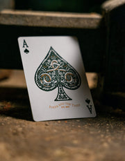 The ace of spades from Edition 5 Playing Cards standing upright on a wooden table. It features green ink and a special copper metallic ink