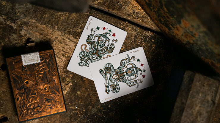 A top down photograph featuring the tuck box and the two joker cards of Edition 5. One Joker card and one Thief card. They both feature green and metallic copper ink