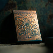 The Tuck Box of edition 5 leaning against a metal box on a wooden table. The lighting illuminates the copper foil on the box
