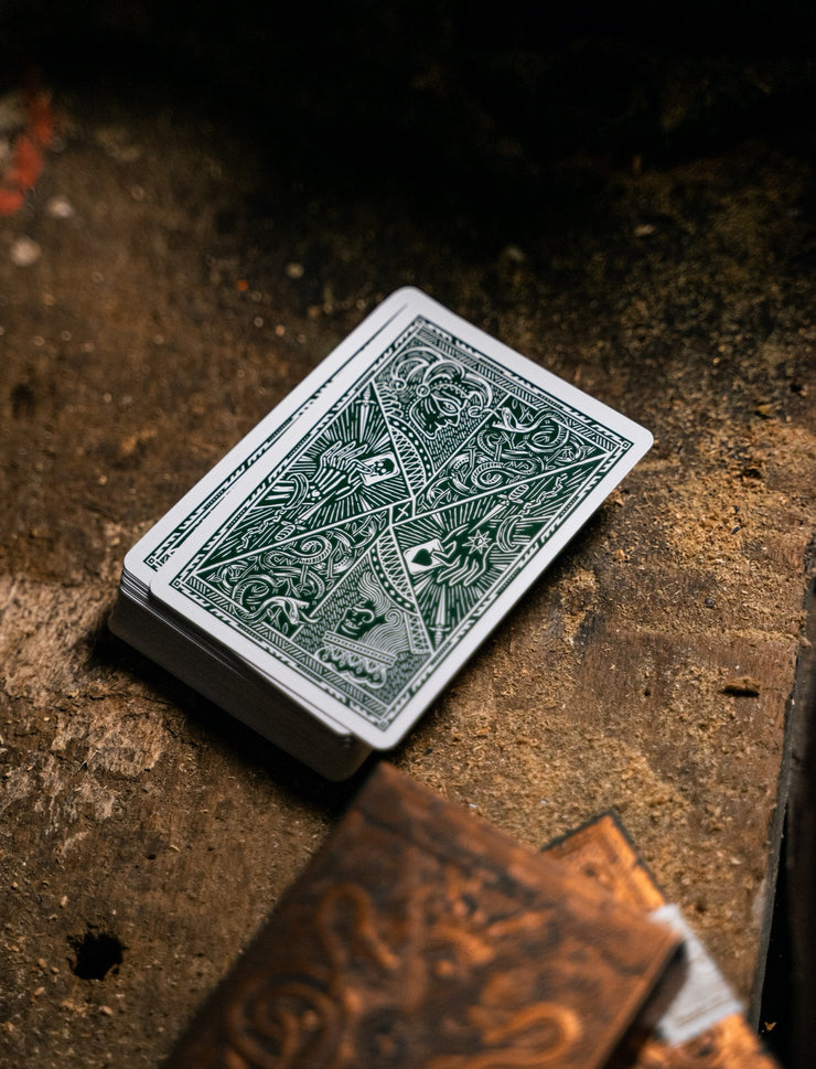 A deck of Edition 5 playing cards on a dusty wooden table displaying the back design