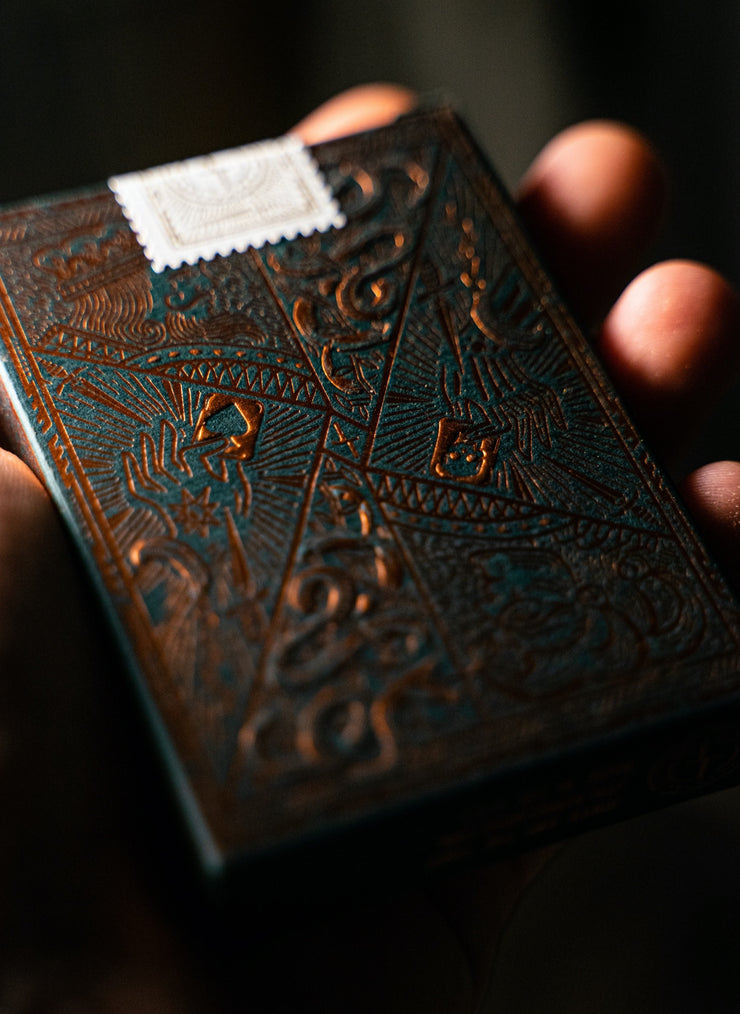 Edition 5 playing cards by Joker and the Thief resting in the palm of a hand. The lighting captures the embossed elements of the tuck box and the copper foil