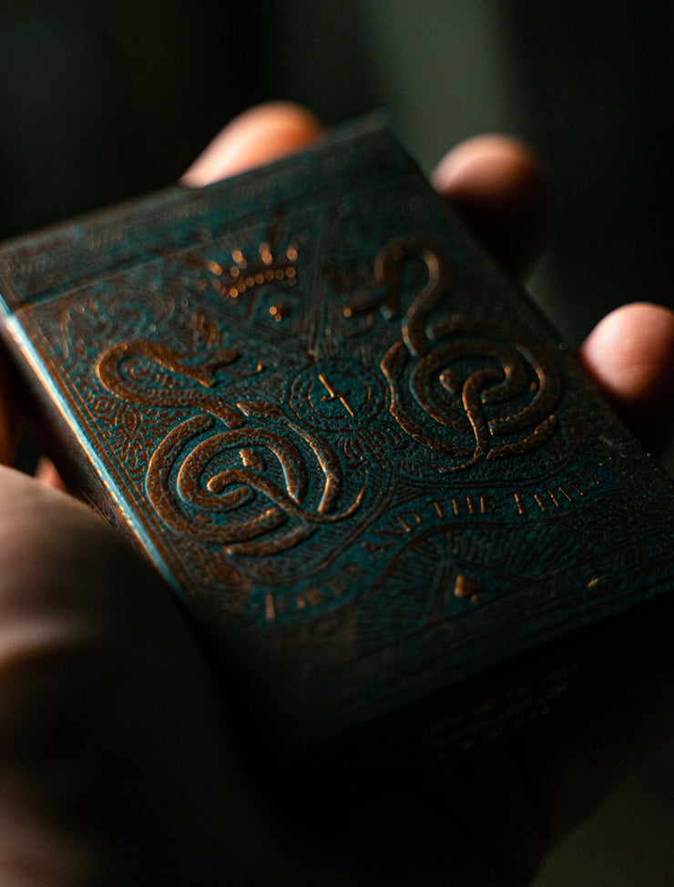 The tuck box of Joker and the Thief Edition 5 held in the palm of a hand. The lighting captures the foil and embossed and raised elements of the front of the box