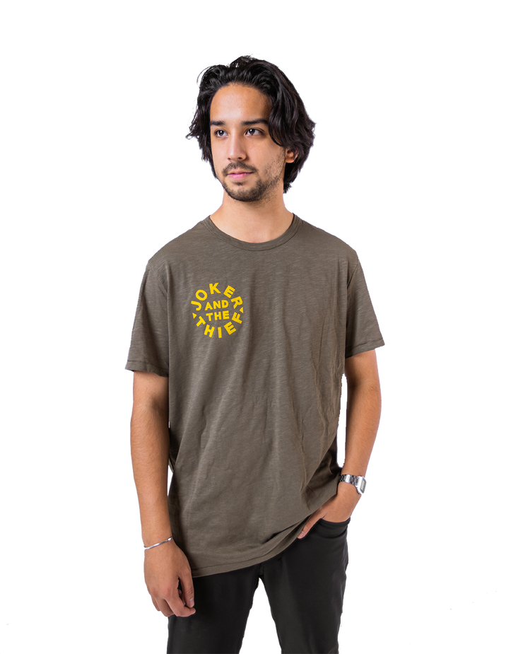 Sean Oulashin from Orbit playing cards modelling the green and yellow joker and the thief cotton t-shirt on a white background.
