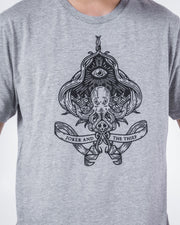 Close up image of a model wearing the Seafarers Spade T-Shirt. The spade features an octopus and third eye with the scrolling company logo at its base.