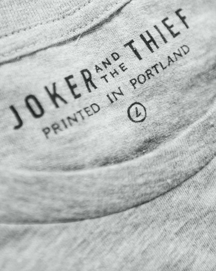 Close up photo showing the expert screen print of the Joker and the Thief logo on the collar of the t-shirt. The tag also demonstrates that the garment was printed in Portland and is a size large in this particular image.