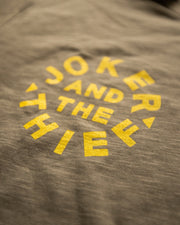 Close up photo of the yellow joker and the thief circular logo screen printed onto the green cotton shirt from alternative apparel.