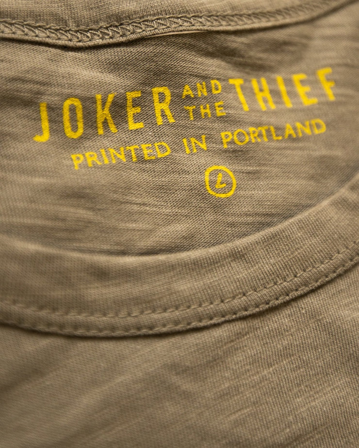A close up image of a green t-shirt detailing the stitching and the yellow tag print on the interior of the collar. The shirt is labeled by Joker and the Thief, is printed in Portland Oregon and is a size Large