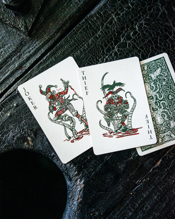 A top down image of three playing cards; two joker from Seafarers and the deck's back design facing down