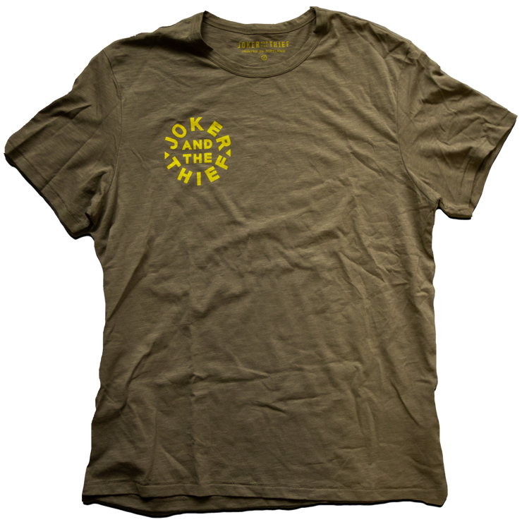 Transparent top down image of a green t-shirt with a bright yellow circle rJoker and the Thief Logo and interior tag