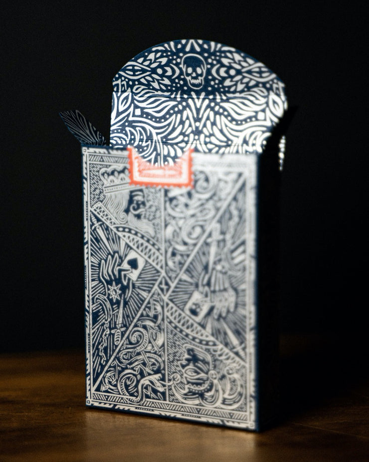 The tuck box of edition 5 standing up on end with its top flaps open. It displays its satin silver foil within the tuck box itself