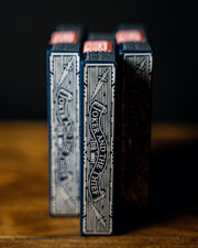 "Three decks of midnight blue stacked on their ends like books on a bookshelf. The side of the tuck box reads ""Joker and the Thief ESTD. MMXV"""