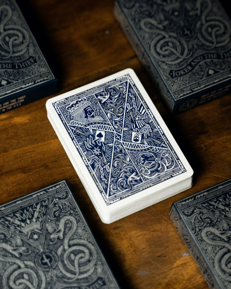 The back design of Midnight Blue Edition Playing Cards surrounded by four tuck boxes of Joker and the Thief playing cards