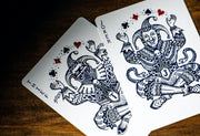 A close up shadowy top down image of the two joker cards of midnight blue edition on a wooden table