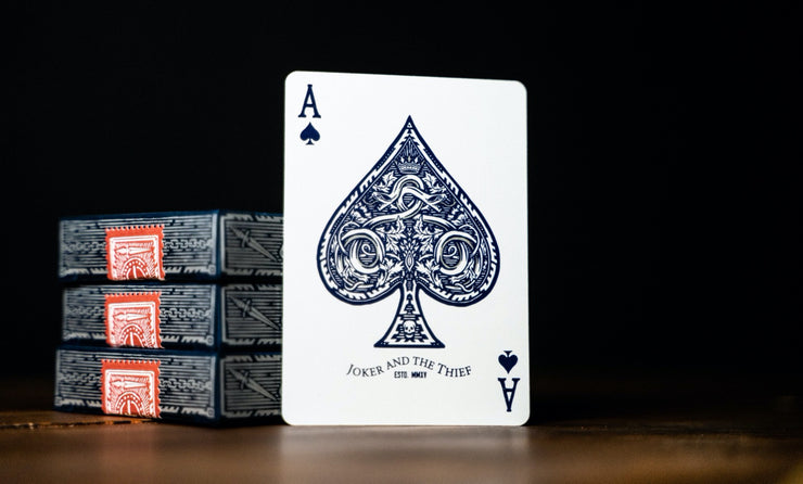 The ace of spades of Midnight Blue Edition playing cards leaning against a stack of three decks.