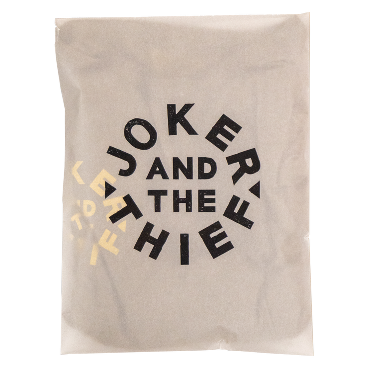 Transparent image of the Joker and the Thief T-Shirt packaging. The green tee is packaged within a custom printed semi-translucent frosted vellum bag