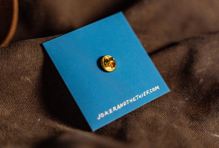 The back clasp of the brass pin fastened to the blue side of its backing card on a rustic canvas surface