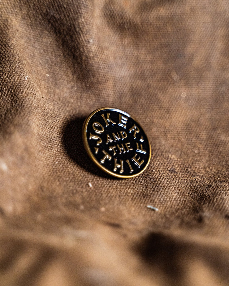 The round black and brass enamel pin reading Joker and the Thief. The surface of the pin is embossed.