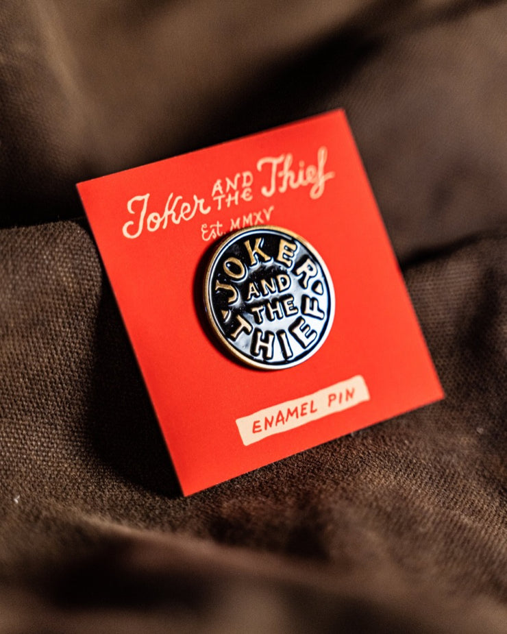 "A round brass and black enamel pin that reads ""Joker and the Thief"" on its red backing card on a waxed canvas surface"
