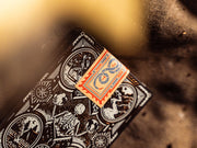 A photo highlighting the seal on the Wayfarers playing cards. The seal is beige in colour and features vibrant red and blue ink with a JT within a coiled serpent
