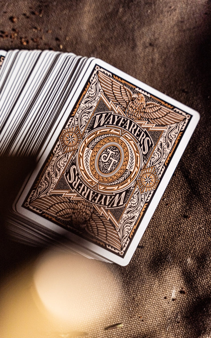 An entire deck of Wayfarers playing cards face down on a waxed canvas surface. The back design features two emboldened eagles with the Joker and the Thief insignia present in the centre and the Wayfarers logo flanking either side.