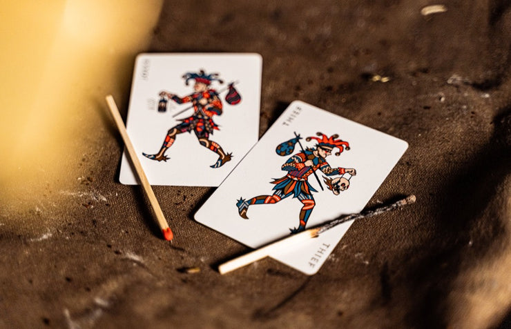 The Joker and the Thief card with two match sticks. One intact, one burned.