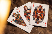 The three diamond court cards overlapping each other on a waxed canvas surface. The jack is holding a bunch of line caught fish. The queen is holding two fishing hooks, and the king is sporting a spear gun and a ribbon fish.