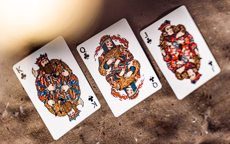 The club court cards from Wayfarers playing cards resting on a waxed canvas surface. The jack, queen and king feature metallic ink, and vibrant red and blue ink.