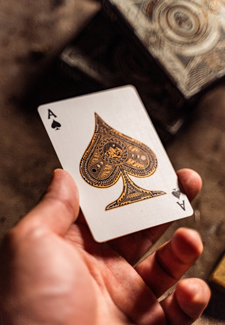 An outstretched hand holds the ace of spades card from the wayfarers deck of playing cards. The lighting of the photo highlights the bronze metallic ink laden on the card. The spade includes details of moon phases, a mountain and a campfire.