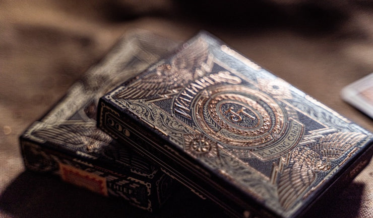 A close up of two decks of Wayfarers playing cards. The embossing and foil of the surface of the box is highlighted. The box is black with eggshell pigment foil and bronze foil