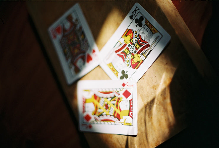 Three traditional Arrco court cards lay on a wooden surface. The three cards consist of the queen of hearts, the king of clubs and the jack of diamonds