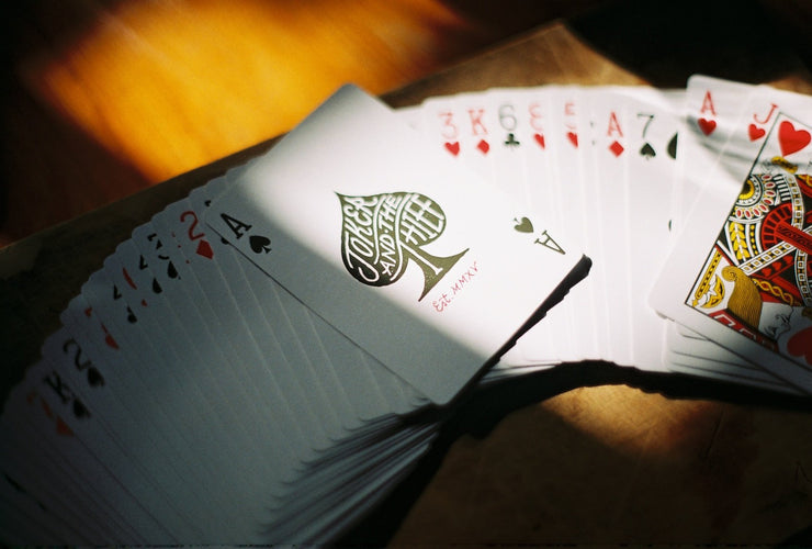 A deck of vintage inspired playing cards spread face up on a wooden board. The green ace of spades is face up, half in the shadows, half in the light